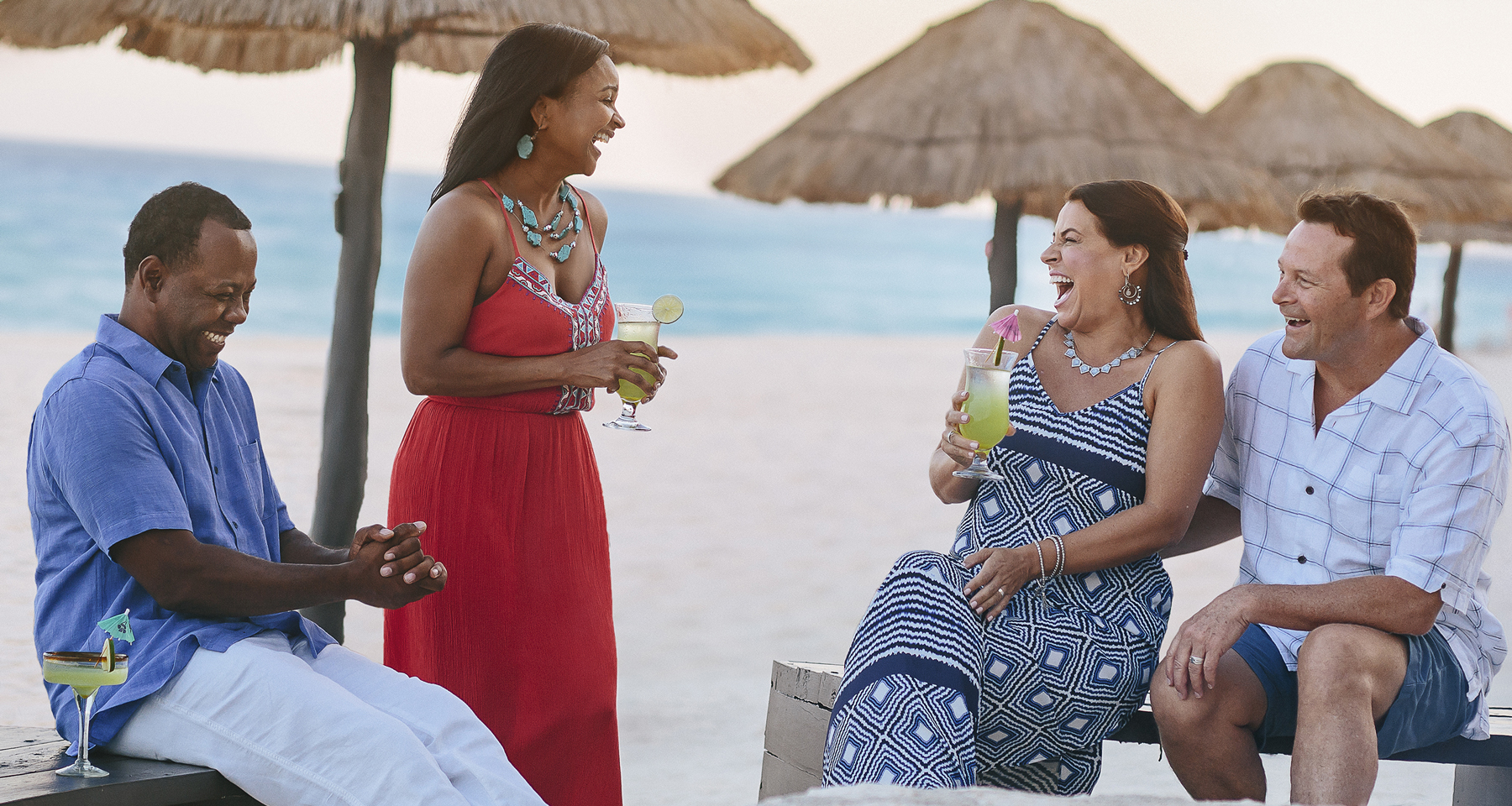 Couples laughing and enjoying drinks on the beach
